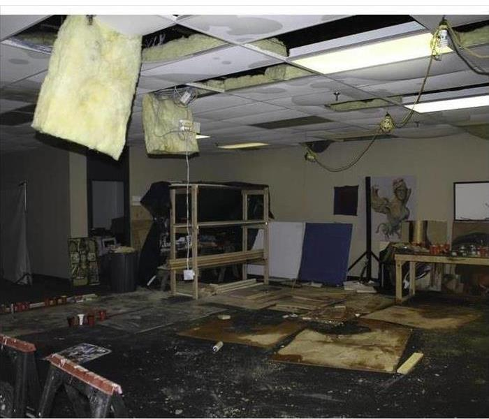 Roof collapsed in a building, many pieces of ceiling tiles on floor, floor wet