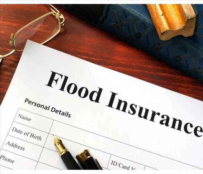 "Desk with a white paper with the title ""Flood Insurance"", there is a pen, glasses and a $50 bill"