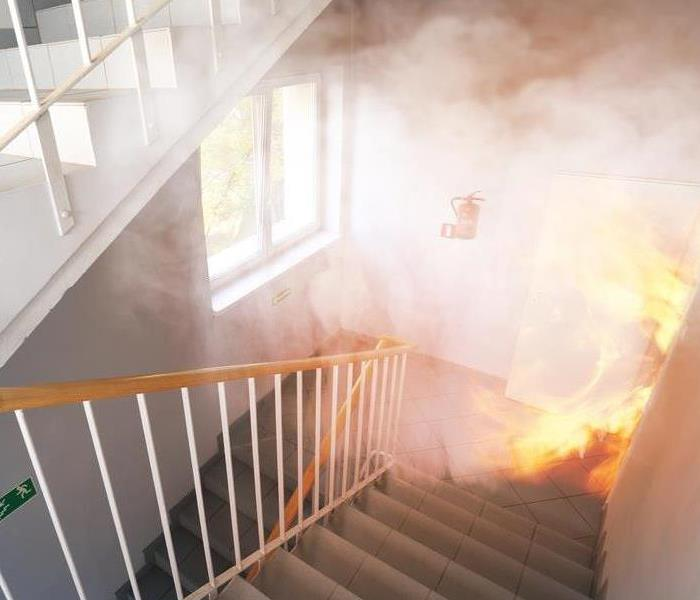 Stairway filled with smoke with fire burning through a doorway.